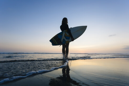 Indonesia, Bali, young woman with surfboard - KNTF00974
