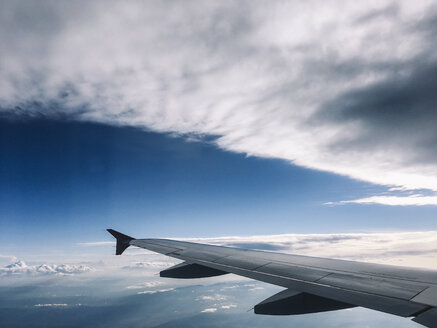 View to wing of airliner flying in gray clouds in the sky. - BZF00378