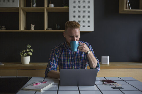 Man drinking coffee and using laptop at home - MOMF00355