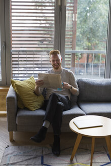 Smiling man sitting on couch at home reading newspaper - MOMF00358