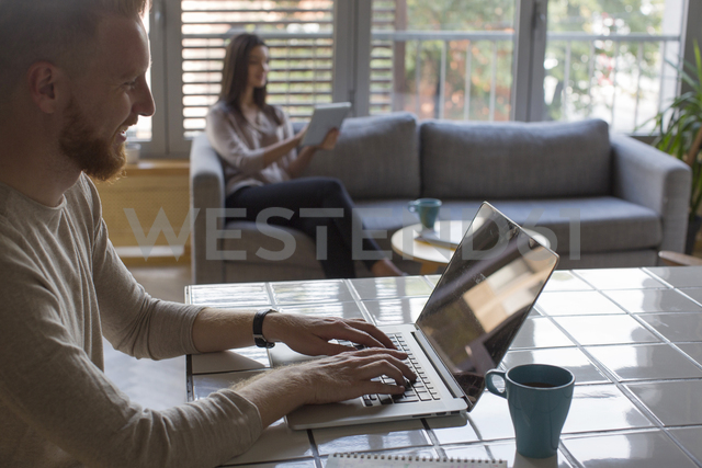 Man with laptop and woman with tablet at home - MOMF00364