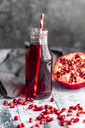 Glass bottle of pomegranate juice and sliced pomegranate - SARF03455
