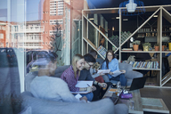 Group of friends sitting together in a cafe with reflection of glass pane - ZEDF01042