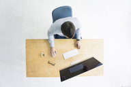 Businessman working at desk in office seen from above - MOEF00634