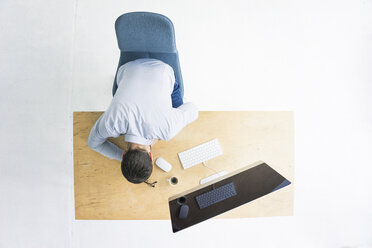 Businessman sitting at desk in office seen from above - MOEF00637