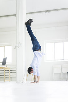 Businessman doing a handstand in office - MOEF00640