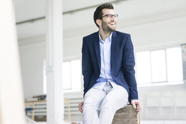 Happy businessman sitting on crate in empty loft office - MOEF00643
