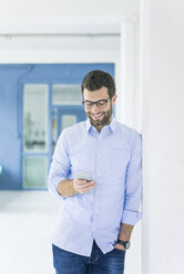 Smiling businessman looking at cell phone in office - MOEF00646