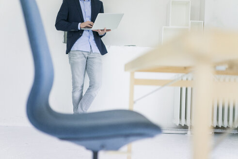 Low section of businessman using laptop in office - MOEF00661