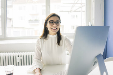 Smiling businesswoman working at desk in office - MOEF00667