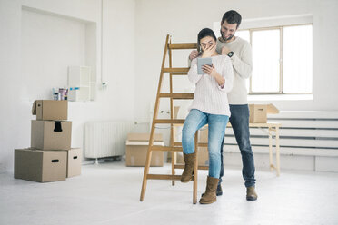 Laughing couple at ladder in new home looking at tablet - MOEF00676