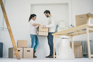 Couple moving into new home unpacking cardboard boxes - MOEF00679