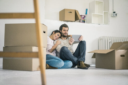 Couple sitting in new home surrounded by cardboard boxes looking at tablet - MOEF00682