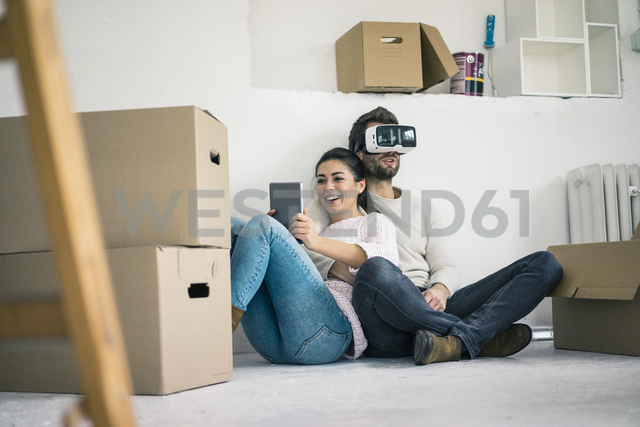 Couple sitting in new home with man wearing VR glasses - MOEF00685
