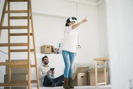Couple in new home with woman wearing VR glasses - MOEF00688