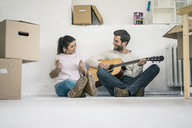 Couple sitting on the floor in new home playing guitar - MOEF00691
