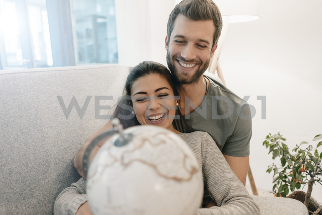 Happy couple on couch at home looking at globe - MOEF00694