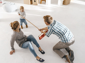 Father and daughter having fun with a broom in a loft - KNSF03387