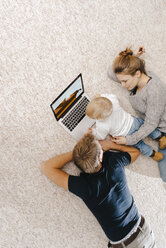 Family using laptop on the carpet - KNSF03390