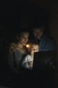 Family using laptop in the dark - KNSF03396