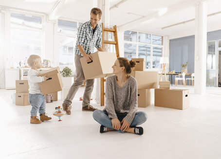 Happy family moving into new home with father and daughter carrying cardboard boxes - KNSF03402