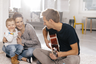 Happy family sitting on the floor with father playing guitar - KNSF03408