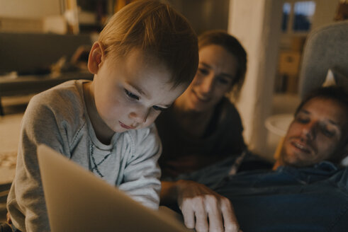 Family using laptop on the couch in the dark - KNSF03414