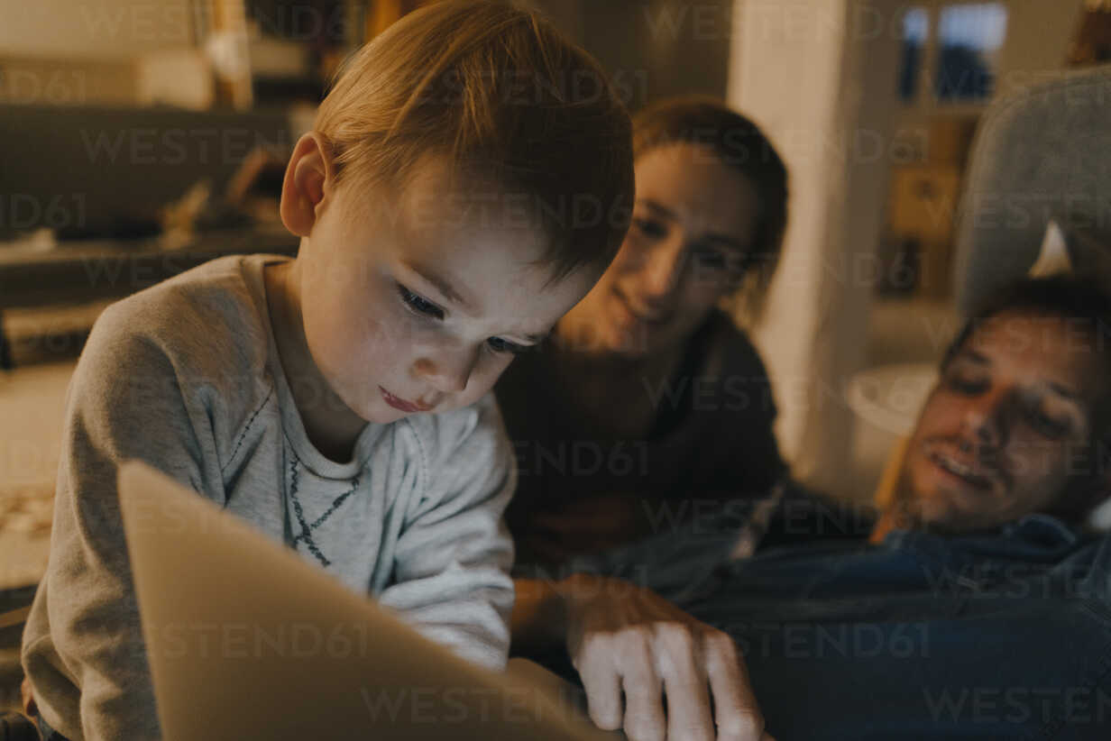 Family using laptop on the couch in the dark - KNSF03414 - Kniel Synnatzschke/Westend61