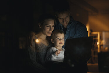 Family using laptop in the dark - KNSF03417