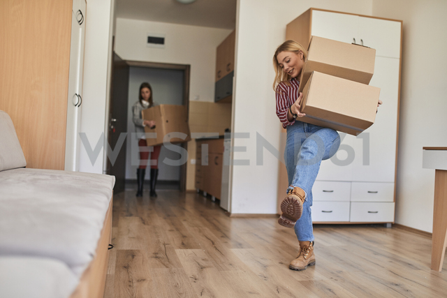 Two young women carrying cardboard boxes into a room - ZEDF01074 - Zeljko Dangubic/Westend61