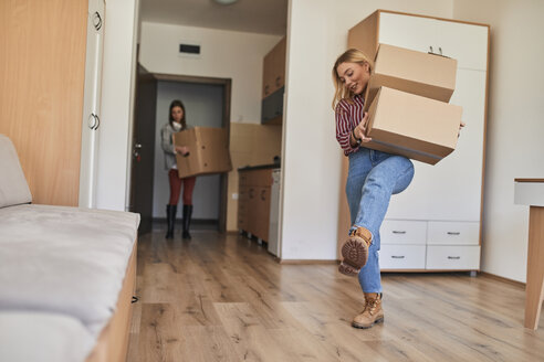 Two young women carrying cardboard boxes into a room - ZEDF01074
