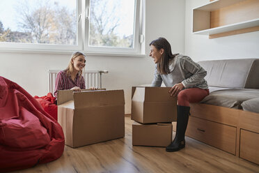 Two happy young women unpacking cardboard boxes in a room - ZEDF01077