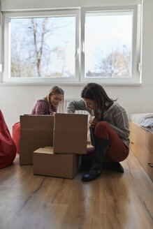 Two young women unpacking cardboard boxes in a room - ZEDF01080