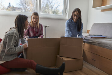 Three happy young women unpacking cardboard boxes in a room - ZEDF01083