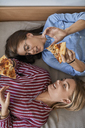 Two young women lying down eating pizza together - ZEDF01095