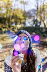 Woman wearing wooly hat blowing soap bubbles in an autumnal forest - MGOF03706