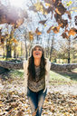 Beautiful happy woman having fun with leaves in an autumnal forest - MGOF03712