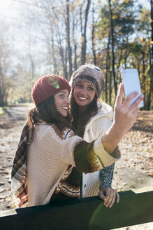 Two pretty women taking a selfie in an autumnal forest - MGOF03715
