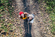 Two happy women standing on an autumnal forest path - MGOF03721