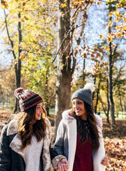 Two pretty women smiling at each other in an autumnal forest - MGOF03724