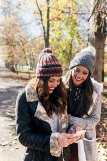 Two happy women with cell phone in autumnal forest - MGOF03727
