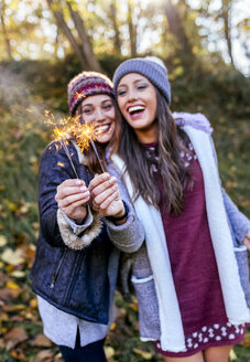 Two happy women holding sparklers in an autumnal forest - MGOF03730