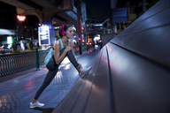 Young woman with pink headphones stretching in the street - SBOF00981