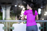 Young woman in pink sportshirt watching urban city lights at night - SBOF00987