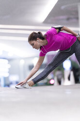 Young woman in pink sportshirt listening to music and stretching in front of modern building - SBOF00990