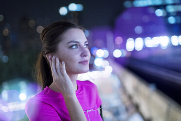 Young woman in pink sportshirt listening to music in city at night - SBOF00993