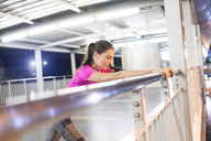 Young woman in pink sportshirt stretching in modern metro station at night - SBOF00999