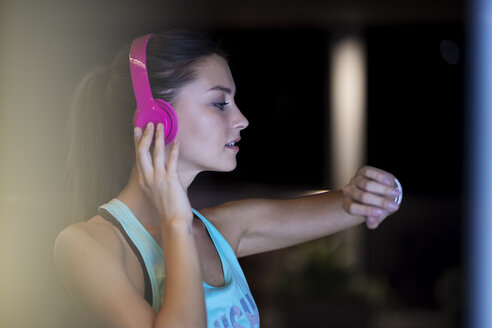 Young woman with pink headphones checking her smartwatch - SBOF01008
