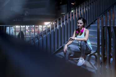 Young woman with pink headphones sitting on stairs and checking her smartwatch - SBOF01014