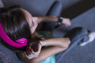 Happy young woman with pink headphones listening to music in modern urban setting at night - SBOF01023